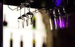 Les verres pour le grappa et les cocktails tropicaux accrochent au-dessus d'un counte de barre Photo stock