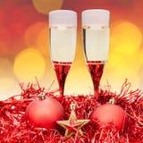Les verres tiennent le premier rôle les babioles rouges de Xmass sur le fond de tache floue photographie stock libre de droits