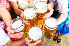 Les verres tintants avec de la bière en bière bavaroise font du jardinage Images libres de droits