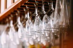Les verres vides pour le vin au-dessus d'une barre étirent Verres de vin accrochants dedans Image stock