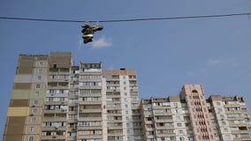 Les vieilles chaussures accrochant haut sur des lignes électriques dans le secteur de ville de dortoir, trafiquants de drogue sig clips vidéos