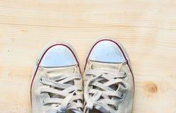 Les vieilles espadrilles sur le fond en bois de plancher et ont l'espace de copie pour Image libre de droits