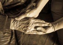 Les vieilles et jeunes mains vérifient le ton de sépia de main Photos stock