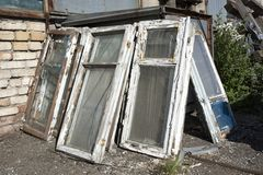 Les vieilles fenêtres dans un cadre en bois avec la peinture blanche minable et le mensonge en verre cassé dans un tas dans la dé Photo libre de droits
