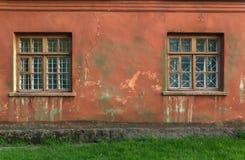 Les vieilles fenêtres endommagées, fenêtres grunges, donnent au mur une consistance rugueuse rouge Photo stock