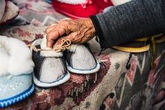 Les vieilles mains femelles froissées tiennent des chaussures du ` s d'enfants Images stock