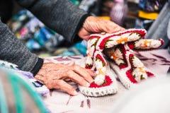 Les vieilles mains femelles froissées tiennent des chaussures du ` s d'enfants Image stock
