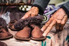 Les vieilles mains femelles froissées tiennent des chaussures du ` s d'enfants Photo libre de droits