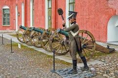 Les vieux canons en bronze dans la cour intérieure de la forteresse de St Peter et de Paul et le mannequin d'artilleur Image stock