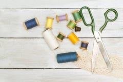 Les vieux ciseaux, bobines du fil, dé sur un backgro en bois Photographie stock