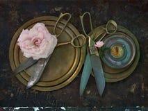 Les vieux ciseaux en métal avec des poignées d'or se touchent des plats de cuivre ronds et d'une rose énorme de rose de thé, le s Image stock