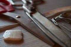Les vieux ciseaux en métal, craie, goupilles de sécurité et mesure de tailleur attachent du ruban adhésif à o photographie stock libre de droits