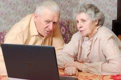 Les vieux couples regardent à l'ordinateur portatif avec l'intérêt actif Photographie stock libre de droits