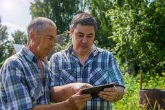 Les vieux et le jeune exploitant agricole discutent au sujet de la récolte images libres de droits