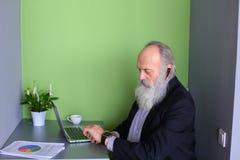 Les vieux hommes retirés avec la barbe travaillent en indépendants et des travaux à distance au compu Image libre de droits