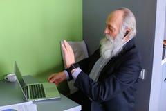 Les vieux hommes retirés avec la barbe travaillent en indépendants et des travaux à distance au compu Photos stock
