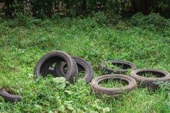Les vieux pneus sales polluent la nature image stock