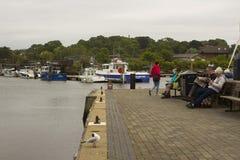 Les visiteurs à la station balnéaire de Lymington détendent sur les bancs en bois par le port un jour frais mat Photographie stock libre de droits