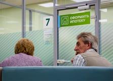 Les visiteurs au centre d'hypothèque attendent une décision sur émettre un emprunt photographie stock