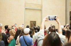 Les visiteurs font des photos de la peinture de Mona Lisa au musée de Louvre Photos libres de droits