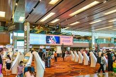 Les visiteurs marchent autour du départ Hall dans l'aéroport Singapour de Changi Image libre de droits