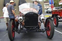 Les visiteurs parlent avec le propriétaire d'un vintage Ford Image stock