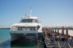 Les visiteurs vers l'île de Robben arrivent en le catamaran de l'eau de V&A Photo libre de droits