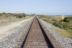 Les voies de voie ferrée fonctionnent à côté de l'océan pacifique Photographie stock