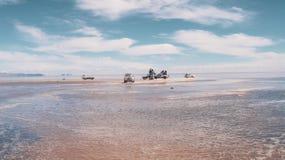 Les voitures alignent pour des appartements de sel en Salar de Uyuni photo libre de droits