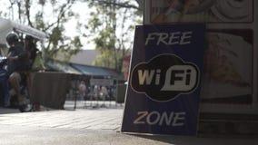 Les voitures asiatiques de peuples de Wi-Fi de rue gratuite d'affiche fait du vélo le signe, symbole banque de vidéos