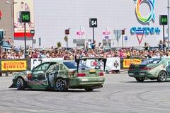 Les voitures de dérive team rond-x écrit la courbure avec le glissement Image stock