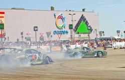 Les voitures de dérive team rond-x écrit la courbure avec le glissement Photo libre de droits