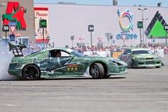 Les voitures de dérive team rond-x écrit la courbure avec le glissement Photographie stock