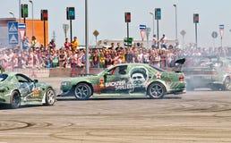 Les voitures de dérive team rond-x écrit la courbure avec le glissement Photos libres de droits
