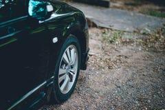 Les voitures et les roues, voiture avant noire ont garé dans la terre le long du photo libre de droits