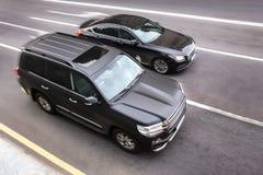 Les voitures noires se déplacent le long de la route Photographie stock