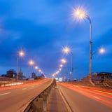 Les voitures passent dessus une route urbaine à la soirée Image libre de droits