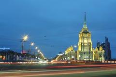 Les voitures s'approchent de l'hôtel Ukraine la nuit Photo stock