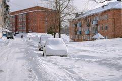 Les voitures se tiennent, couvert de neige, dans le village images stock