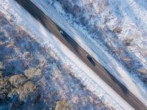 Les voitures sur la route en hiver avec la neige ont couvert la vue aérienne d'arbres photo stock