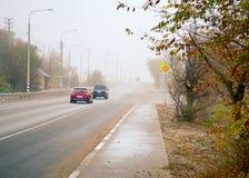 Les voitures vont sur l'itinéraire en automne à une brume de brouillard Images libres de droits