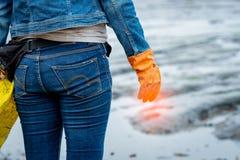 Les volontaires utilisent des jeans et de longues chemises gainées et portent les gants en caoutchouc oranges pour rassembler des photographie stock libre de droits