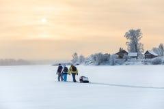 Les voyageurs d'hiver trimardant sur le lac glacent au coucher du soleil au-dessus d'un village Photographie stock