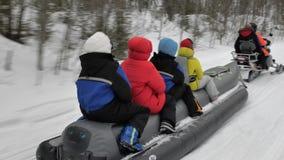Les voyageurs dans des vestes colorées s'asseyent sur le bateau de banane gris de neige clips vidéos