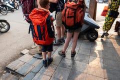 Les voyageurs de famille avec le sac à dos lourd soutiennent dessus sur la rue de l'Asie Photo stock