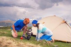 Les voyageurs drôles s'asseyent à côté de la tente, faisant cuire la nourriture Photographie stock