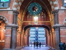 Les voyageurs marchent par l'entrée avant arquée de la station de Saint-Pancras, Londres, Angleterre, à l'époque de Noël Images stock