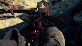 Les voyageurs se réchauffent les pieds par le feu de camp dans les montagnes clips vidéos