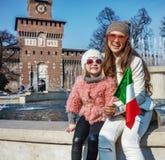 Les voyageuses de mère et de fille près de Sforza se retranchent montrer le drapeau Photographie stock libre de droits