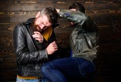 Les voyous brutaux d'hommes portent le combat de vestes en cuir Attaque physique Combat barbu de hippie d'hommes Attaque et défen photo stock